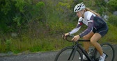 конкурент : Concentrated female cyclist cycling on a countryside road 4k