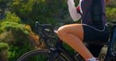 concorrentes : Young female cyclist wearing sunglasses in countryside road 4k