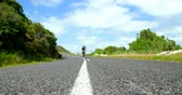 конкурент : Female cyclist cycling on a countryside road on sunny day 4k