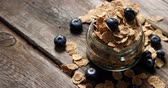 kőműves : Jar filled with wheat flakes and blueberries on a wooden table 4k
