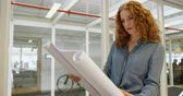 ruivo : Female architect looking at blueprint in office 4k