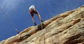 góral : Mountaineer rappelling down the hill with the help of rope on a sunny day 4k