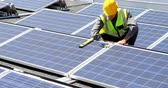 renewable sources : Male worker working at solar station on a sunny day 4k
