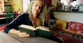literatura : Mature woman reading a book in living room at home 4k Vídeos