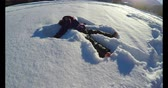 szórakozási : Kid making snow angels in snow during winter on a sunny day 4k