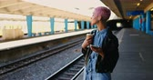 nose ring : Pink hair woman listening music on mobile phone in railway station 4k Stock Footage