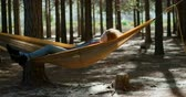 os olhos fechados : Young woman sleeping on a hammock in the forest 4k Vídeos