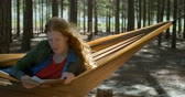 függőágy : Young woman reading a book in the forest 4k Stock mozgókép