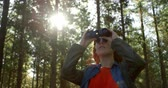 dürbün : Young woman looking through binoculars in the forest 4k
