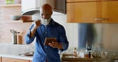 domicílio : Senior man using digital tablet while having black coffee in kitchen at home 4k Stock Footage