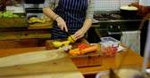 doğrama : Mid section of woman chopping vegetables in cafe kitchen 4k Stok Video