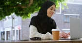 disposable cup : Woman in hijab working on laptop at outdoor cafe 4k Stock Footage