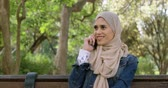 interagindo : Woman in hijab talking on mobile phone in the garden 4k