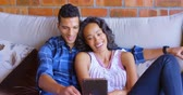 domicílio : Couple using digital tablet on sofa at home 4k