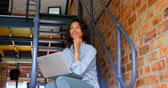 domicílio : Smiling woman with laptop sitting on stair at home 4k Stock Footage