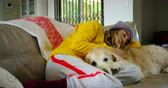 engedelmes : Woman relaxing on sofa with her dog at home 4k Stock mozgókép