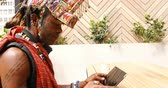 tablet pc : Tribal man using digital tablet in outdoor cafe 4k