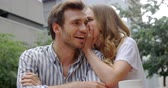 casual sitting : Woman whispering  in mans ear at outdoor cafe 4k Stock Footage