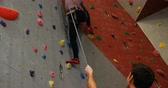 stamina : Coach assisting a woman in climbing the artificial wall at bouldering gym 4k