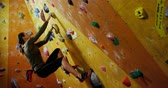 западный : Courageous woman climbing the artificial wall at bouldering gym 4k Стоковые видеозаписи