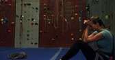postroj : Depressed woman sitting against the artificial wall at bouldering gym 4k