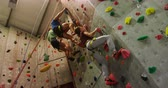 postroj : Low angle view of men and woman climbing an artificial wall at bouldering gym 4k