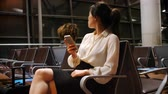 texting : Commuter using mobile phone in waiting area at airport terminal 4k