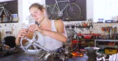állítsa : Beautiful woman repairing parts of bicycle at workshop 4k