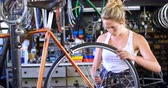 oiling : Beautiful woman oiling bicycle at workshop 4k Stock Footage