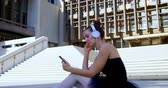 sukénka : Female ballet dancer listening music on mobile phone on the pavement 4k
