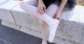 sukénka : Female ballet dancer tying the ribbon on her ballet shoes on retaining wall 4k Dostupné videozáznamy