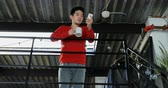 korkuluk : Man with coffee cup using mobile phone on railing at home 4k