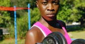 determined : Portrait of female athlete exercising with dumbbell in the park 4k