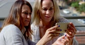 lesbian : Lesbian couple using mobile phone in balcony at home 4k