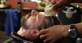 среднего возраста : Close up of barber washing mans hair at barbershop 4k