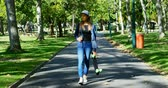 skateboard : Beautiful woman with skateboard walking on street near park 4k