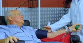 blood supply : Senior man interacting with physician while donating blood in blood bank 4k Stock Footage