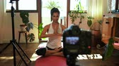 napló : Female video blogger recording video about yoga at home 4k