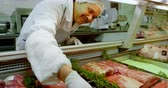 display case : Smiling butcher arranging meat in refrigerator at shop 4k Stock Footage