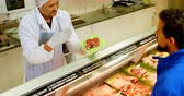 display case : Overhead of butcher selling meat to customer at shop 4k