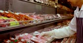 display case : Butcher arranging wrapped meat in rack at shop 4k