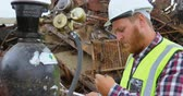 hurda : Male worker examining gas cylinder in the junkyard 4k Stok Video