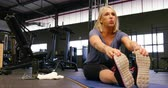 pó : Determined senior woman stretching in fitness studio 4k