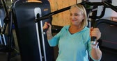 determined : Senior woman doing exercise on chest press machine in fitness studio 4k