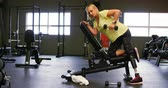 determinado : Senior woman doing dumbbell row exercise in fitness studio 4k