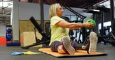 determined : Senior woman doing oblique exercises on exercise mat in fitness studio 4k