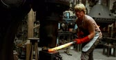 kovács : Blacksmith shaping hot metal rod in machine at workshop 4k