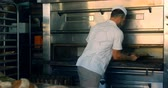 chef uniform : Baker removing freshly baked bread bun from the oven 4k