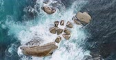 dinginlik : Aerial of waves splashing o the rocks amidst the sea 4k Stok Video
