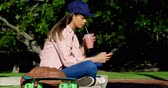 skateboarding : Woman using mobile phone while having juice on a sunny day 4k